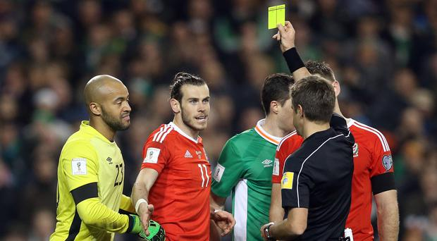 Gareth Bale, second left, was not happy to receive a yellow card for his challenge on John O'Shea