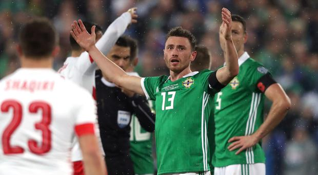 Corry Evans reacts in disbelief after conceding a penalty against Switzerland
