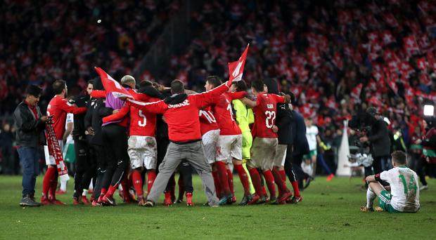 Stuart Dallas, right, sits dejected and watches Switzerland's celebrations