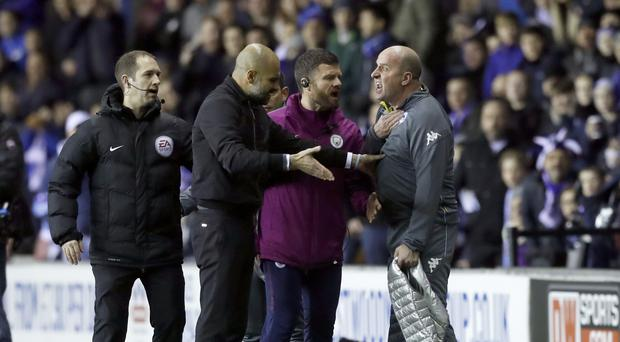 Pep Guardiola (second left) and Paul Cook (right) argued after Fabian Delph was controversially sent off at Wigan