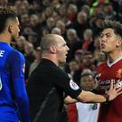 Referee Bobby Madley keeps Roberto Firmino, right, and Mason Holgate apart