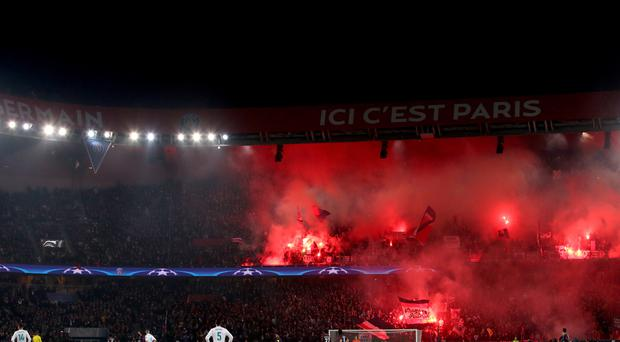 Fans in the stands light red flares during the match in order to show their support
