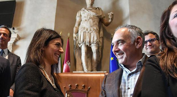 Roma president James Pallotta, right, shakes hands with Rome Mayor Virginia Raggi after donating 230,000 euros to pay for the restoration of a fountain in the city