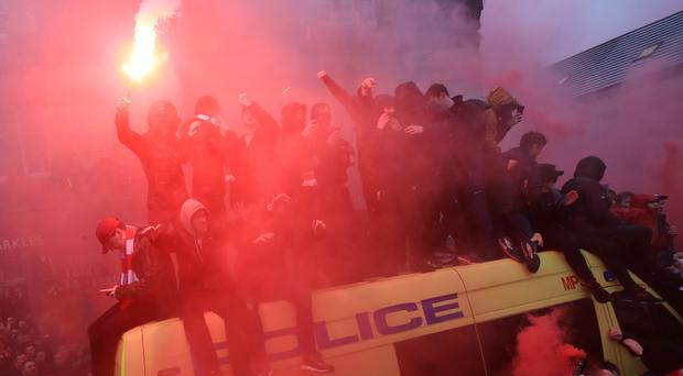 Fans on top of a police van were seen with flares before kick-off