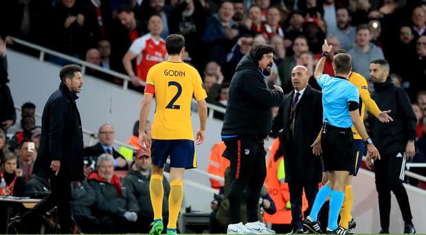 Atletico Madrid manager Diego Simeone (left) is sent to the stands by match referee Clement Turpin as assistant coach German Burgos (centre) gestures