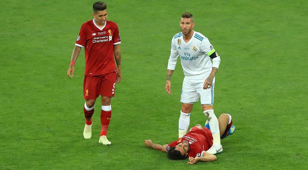 Sergio Ramos stands over Mohamed Salah after a challenge that injured the Liverpool forward (Peter Byrne/PA)