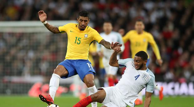 Brazil's Paulinho (left) is challenged by England's Joe Gomez during the Bobby Moore Fund International match at Wembley Stadium, London.