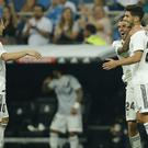 Marco Asensio, right, celebrates his goal with Luka Modric, left and Dani Ceballos (Paul White/AP)