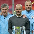 Manchester City manager Pep Guardiola and his backroom staff pose with the Carabao Cup trophy (Nick Potts/PA)