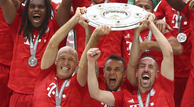 Arjen Robben, front left, and Franck Ribery, front right, lift the trophy to celebrate Bayern's seventh straight Bundesliga title (Matthias Schrader/AP)