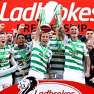 Celtic's Scott Brown (centre) and Mikael Lustig celebrate with the trophy after winning the Ladbrokes Scottish Premiership match at Celtic Park, Glasgow.