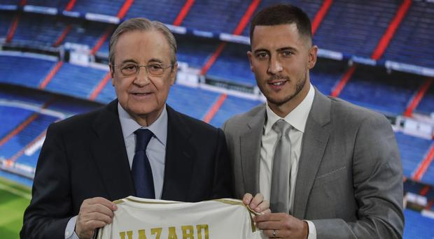 Eden Hazard, right, holds his new shirt with Real Madrid's president Florentino Perez (Manu Fernandez/AP)