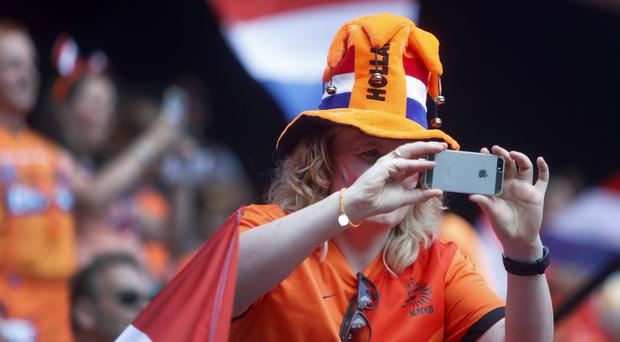A fan holds a mobile phone prior to the Women's World Cup match between the Netherlands and Cameroon (Michel Spingler/AP)