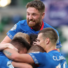 You beauty: Linfield players, including Mark Stafford (top), rush to congratulate scorer Shayne Lavery