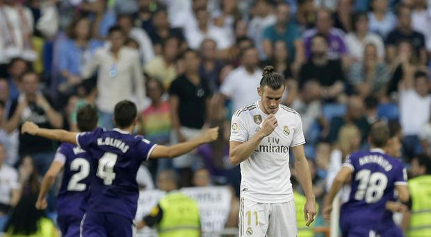 Real Madrid's Gareth Bale, centre, shows his disappointment as Real Valladolid celebrate (Paul White/AP)