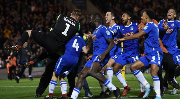 Colchester players jump on Tom Lapslie after he scores the winning penalty (Joe Giddens/PA)