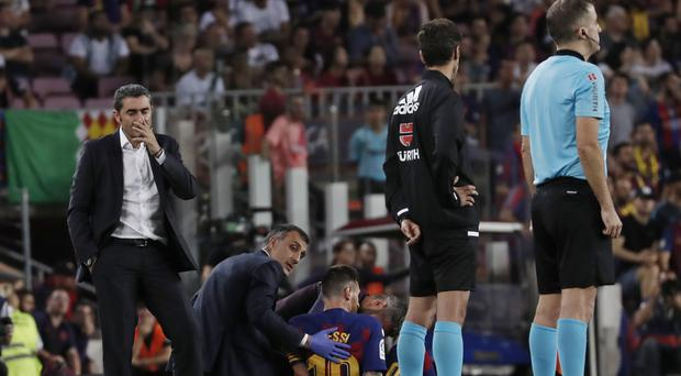 Lionel Messi was injured in the first half of his side's win over Villarreal (Joan Monfort/AP)