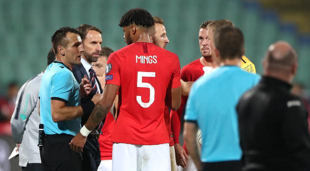 Referee Ivan Bebek (left) speaks to England manager Gareth Southgate and Tyrone Mings following some racist chanting (Nick Potts/PA)