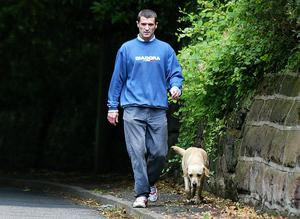 Roy Keane walks his dog outside his home in Hale Barnes after being sent home from the World Cup (Martin Rickett/PA)