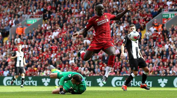 Liverpool's Sadio Mane (top) jumps over Newcastle United goalkeeper Martin Dubravka to score his side's second goal of the game during the Premier League match at Anfield, Liverpool.