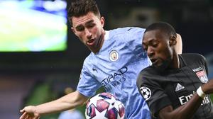 Manchester City's Aymeric Laporte, left, and Lyon's Karl Toko Ekambi battle for the ball during the Champions League quarter-final in Lisbon (Franck Fife/Pool Photo via AP).