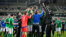 Bumpy road: Michael O'Neill is lifted high by his team after last night's  win over Greece at Windsor Park