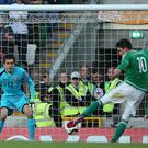 The one that got away: Kyle Lafferty pulls the trigger, but his effort was saved by Romania goalkeeper Ciprian Tatarusanu