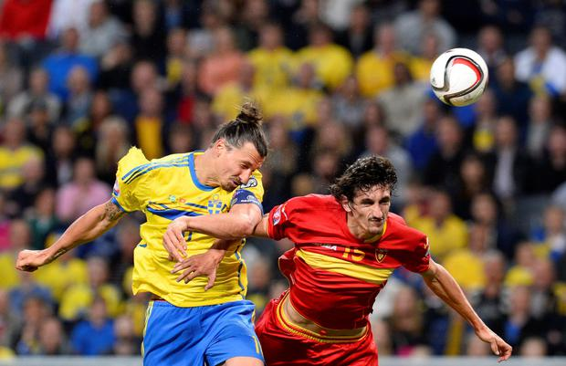 Swede success: Zlatan Ibrahimovic of Sweden beats Montenegro's Stefan Savic in an aerial challenge