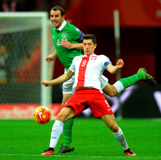 Strength: Poland's Robert Lewandowski holds off the challenge of John O'Shea