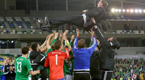 High jump: Manager Michael O'Neill is thrown into the air by his Northern Ireland players after Euro 2016 qualification was secured