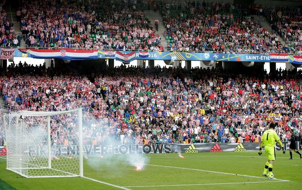 Czech Republic goalkeeper Petr Cech, right, looks at burning flares thrown on to the pitch from the stands during the Euro 2016 Group D soccer match between the Czech Republic and Croatia at the Geoffroy Guichard stadium in Saint-Etienne, France, Friday, June 17, 2016. (AP Photo/Pavel Golovkin)