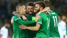 Here oui go: Northern Ireland's Steven Davis, Oliver Norwood and Stuart Dallas celebrate defeating Greece to book their place in France for the Euro 2016 finals