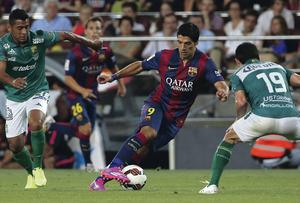 Look who's back: Barcelona's Luis Suarez fights for the ball against Leon's Luis Antonio Delgadot and Jonny Magallon