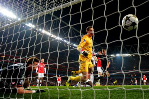 LONDON, ENGLAND - FEBRUARY 19: Wojciech Szczesny of Arsenal scrambles in vain to prevent the ball crossing the line as goalscorer Mario Mandzukic of Bayern Muenchen watches from inside the goal during the UEFA Champions League round of 16 first leg match between Arsenal and Bayern Muenchen at Emirates Stadium on February 19, 2013 in London, England. (Photo by Shaun Botterill/Getty Images)