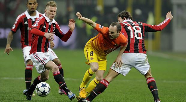 MILAN, ITALY - FEBRUARY 20: Andres Iniesta of FC Barcelona (C) competes for the ball with Riccardo Montolivo of AC Milan #18 during the UEFA Champions League Round of 16 first leg match between AC Milan and Barcelona at San Siro Stadium on February 20, 2013 in Milan, Italy. (Photo by Claudio Villa/Getty Images)