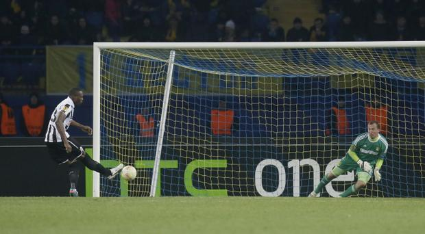 Shola Ameobi of Newcastle United scores a penalty past FC Metalist Kharkiv goalkeeper Olexandr Goryainov during a Europa League round of 32 second leg soccer match in Kharkiv, Ukraine, Thursday, Feb. 21, 2013.(AP Photo/Efrem Lukatsky)
