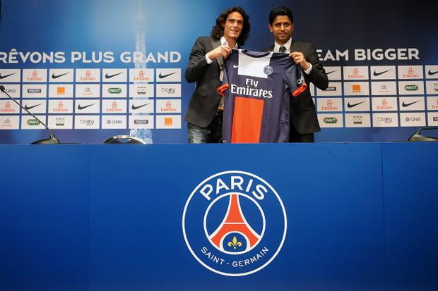 PARIS, FRANCE - JULY 16: Paris Saint-Germain's (PSG) new forward, Edinson Cavani (L), and Paris Saint-Germain's (PSG) chairman Nasser Al-Khelaifi, pose with Cavani's jersey during a press conference on July 16, 2013 in Paris, France. Cavani's transfer to Paris Saint-Germain football club is reported to have cost in the region of ?55m. (Photo by Antoine Antoniol/Getty Images)