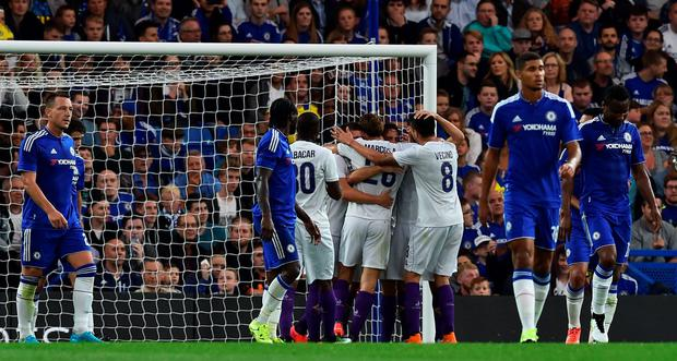 Up and down: Chelsea players are dejected as Fiorentina celebrate Gonzalo's goal last night in the Champions Cup match at Stamford Bridge