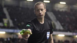 Referee Willie Collum removes a bottle from pitch during Hibernian's William Hill Scottish Cup quarter final match with Celtic (Graham Stuart/PA)