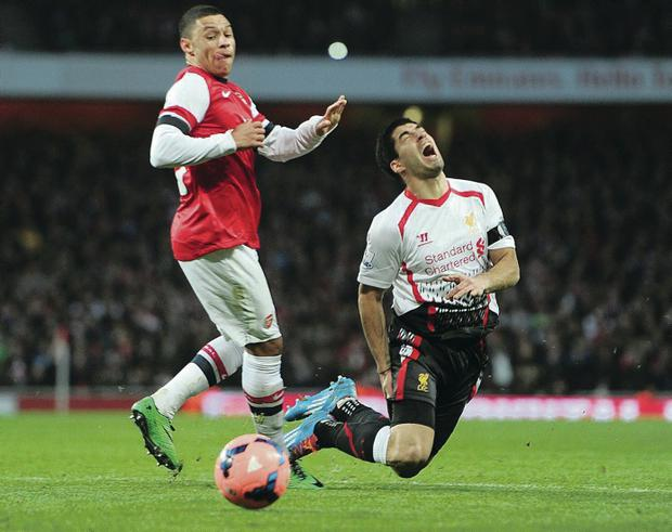Liverpool's Luis Suarez falls in agony after being challenged by Arsenal's Alex Oxlade-Chamberlain
