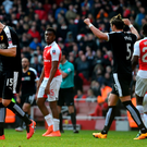 Joy and pain: Northern Ireland and Watford ace Craig Cathcart (left) leads the celebrations as holders Arsenal are knocked out of the FA Cup at the Emirates