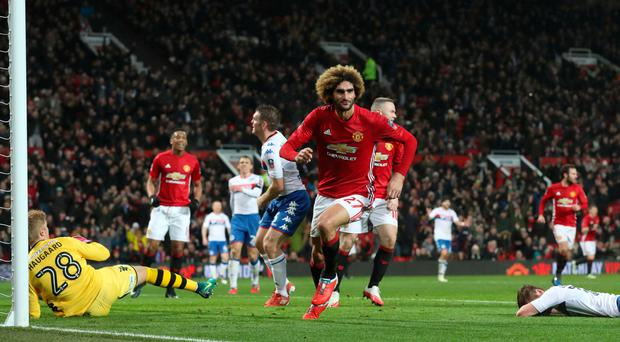 Up and running: Marouane Fellaini wheels away after putting United in front at Old Trafford