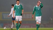 Gareth McAuley (left) and Chris Brunt walk off the pitch after the 2-0 defeat by Israel