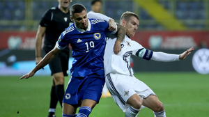 Arm's length: Steven Davis fights for possession with Bosnia ace Rade Krunic during the Euro play-off semi-final in Sarajevo