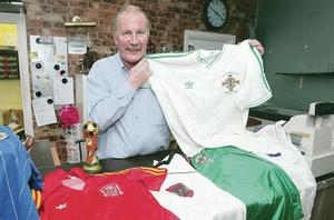 Getting shirty: Northern Ireland legend Billy Hamilton shows off his impressive collection of football shirts from the 1982 and 1986 World Cups at his trophy shop in Bangor