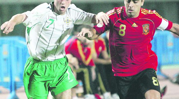Ivan Sproule (left) battles it out with Xavi during Northern Ireland's game with Spain back in 2007
