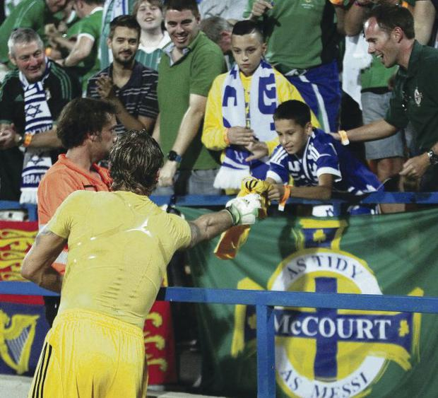 Northern Ireland goalkeeper Roy Carroll gives his shirt to a fan after their 1-1 draw against Israel