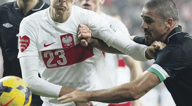 Up close: Jon Walters (right) of the Republic of Ireland battles with Poland's Lukasz Teodorczyk in the 0-0 draw in Poznan