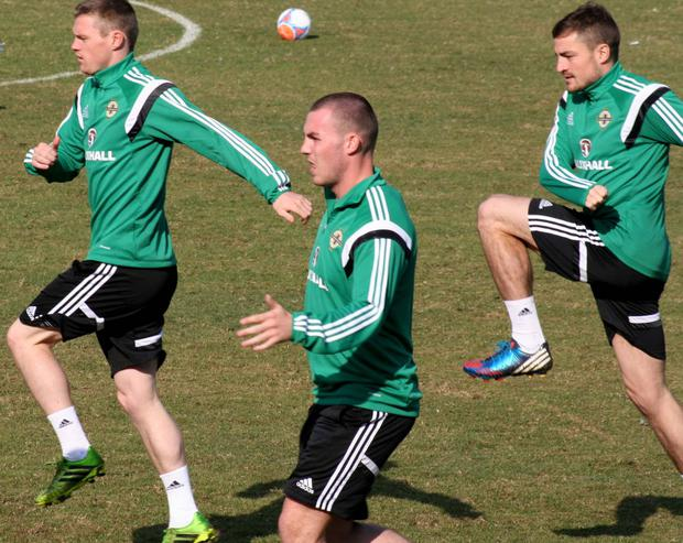 Warming up: Northern Ireland players Billy McKay, Luke McCullough and Paul Paton train in Montevideo yesterday
