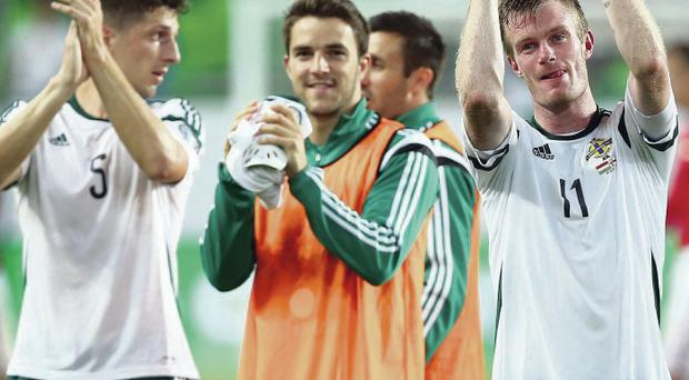 Glory boys: Craig Cathcart, Andrew Little and Chris Brunt applaud the Green and White Army in Budapest